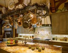Suspended above the island is a handforged, iron pot rack adorned with Italian names of herbs  The plaster and steel range hood repeats the Italian herbal detail and creates a focal point while counterpointing the classic style of the Wolf range  Kitchen  TraditionalNeoclassical by Sherry Hayslip Interiors & Hayslip Design Associates, Inc