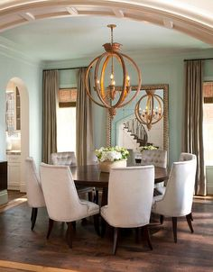 An arched doorway leads to a stunning blue and taupe dining room lined with walls painted in Sherwin Williams North Star framing windows dressed in long taupe curtains and bamboo roman shades flanking hammered metal floor mirror reflecting a dark brown round dining table seating nine light gray velvet tufted dining chairs lit by Currey & Co Dauphin Chandelier.