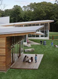 Jardín de la Ciencia en Children's Schools en Stamford, USA. Grandes rocas sustituyen el equipamiento convencional para incentivar el juego creativo. Se recolecta agua de la lluvia a través de barriles.:
