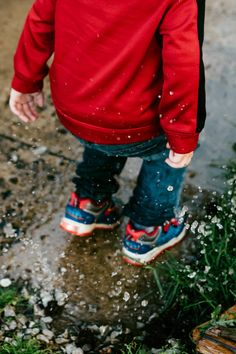 Boy in Red Jacket Jumping on Concrete Walkway Near Grass during Daytime