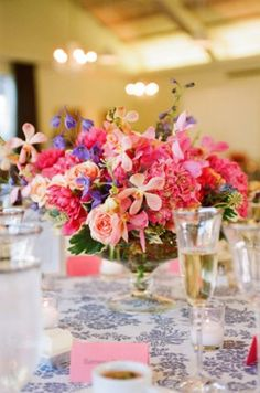 Bright pink floral centerpiece with violet and peach accents - Photo by Sylvie Gil Photography