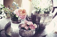 Old metal teapots filled with flowers