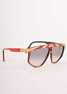 Vintage sunglasses have small keyhole at center between lenses.?Íí_ ?Íí_ Made in: Unknown Color: Red, Gold, Black Fabric Content: Unknown, appears to be resin. Condition: Good. Slight scratching.?Íí_