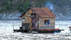 a tiny fixer upper house afloat in the water
