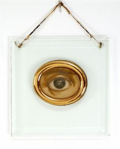 early 20th c. EYE DOCTOR'S SIGN Eye painted on wood surrounded by a gilt metal bezel, mounted on a glass plaque...
