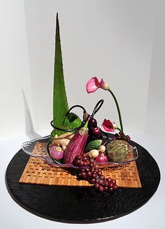 Art Loop Ikebana Exhibition 6-3-16 By Jeanne  Title: Produce In Motion  Theme: Free Style - Using Fruits and/or Vegetables in an Arrangement  Materials: Aloe Vera Prickly Pear Cactus Ginger Turnip Grapes Chinese Eggplant Red Onion Artichoke Spicy Asian Cucumber Calla Lily