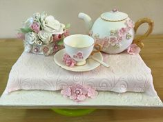 Gumpaste teapot, cup and saucer with spoon and a flower bouquet sits on a Victoria sponge table covered in a fondant tablecloth.