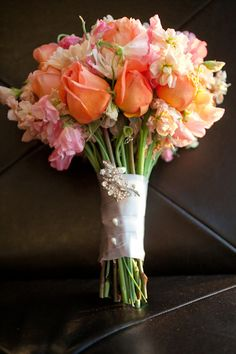 Pink, peach, and coral rose and sweet pea clutch bouquet with no foliage.