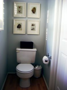 decoration lovely small bathroom wall decor ideas using set of 4 framed pictures over white porcelain toilet and small plastic trash can alongside stainless steel paper towel holder