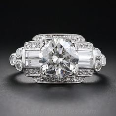 A consummate Art Deco style platinum and diamond engagement ring blazing front and center with a gorgeous and glistening transitional European/round brilliant-cut diamond, weighing just a handful of points shy of 2.00 carats. The diamond is majestically displayed between two pairs of shimmering baguette diamonds bordered by small round diamonds which, in turn, lead to a twinkling trefoil motif on each lateral side. North and south, the diamond is enlivened by a slightly lowered tier of round…