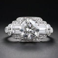 A finales del Art Deco anillo de platino y de compromiso de diamantes consumada ardiente frente y al centro con una hermosa y brillante de transición diamante / redondo talla brillante Europea, un peso de sólo un puñado de puntos tímidos de 2,00 quilates. El diamante se muestra majestuoso entre dos pares de diamantes baguette brillantes bordeadas por pequeños diamantes redondos que, a su vez, conducen a un motivo trébol abrir y cerrar de cada lado lateral. Norte y Sur, el diamante está…