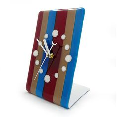 """Modern Fused Glass Desk Clock: Candy Stripe. Conventional clock numerals are replaced with simple white circles, contrasting against the robust shades of blue, maroon, and mocha in bold vertical stripes. The lively design is permanently fused by means of kiln-firing the glass at extreme temperatures. With the addition of clock hands, the fused glass becomes an admirable work of functional art for your contemporary space! Measures approximately 8"""" tall. Requires 1 'AA' battery."""