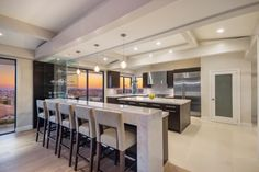 Casual dining gets the luxurious benefit of incomparable views and a white marble eating bar in this open plan kitchen. The design is modern with the focus on the large windows and sleek, efficient feel.