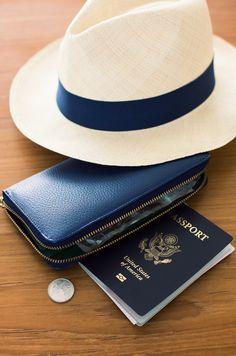 Travel essentials: passport, leather travel wallet (designed to fit passport!), and straw panama hat. Bon voyage!