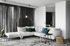Living room: pale grey modular sofa with chaise longue, green and blue scatter cushions, black side table, black and wooden nesting tables, black sheer curtains, white walls with wooden panelling, pale grey rug
