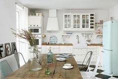 White shaker-style kitchen, with white splash-back tiles and oak worktops