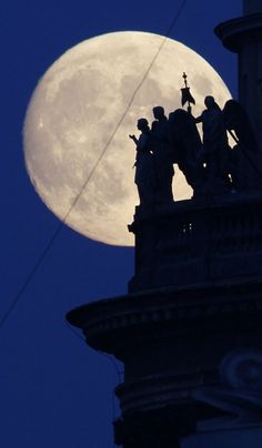 Statues of angels silhouetted on the full moon in St.Petersburg, Russia.