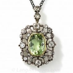 Georgian Antique Green Beryl and Diamond Pendant - A gorgeous 5.15 carat light yellowish green beryl (the same material as emerald, but a lighter hue) is framed by an openwork scroll motif glittering with 1.50 carats of old mine-cut diamonds set in silver. This is a lovely early nineteenth century Georgian jewel, most likely originating from Great Britain.