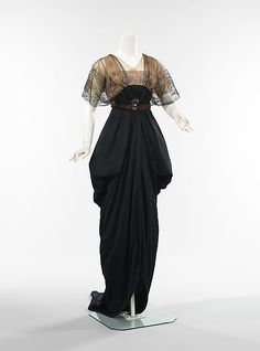 Dinner dress, House of Drécoll, 1912-13. The classic pannier draping and long pointed train of this dress indicates the highest style of the period. Beautiful in shape and style, the piece is an elegant combination of refined materials and intricate handwork. A well-thought out and interesting detail, the semi-circular shape of the brooch mimics the shape of the bodice.