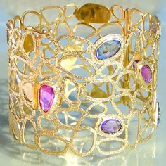 Materials 18k Gold and 7 Sapphires. Specifics The bracelet is 2 inches wide. It weighs 44 grams.