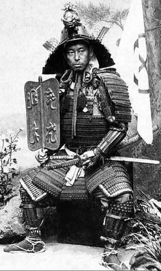 """Nobukuni Enami 江南 信國 (1859-1929) was the real name of Yokohama photographer T. Enami. Here he is wearing armor and holding a gunsen (war fan) in a moment of repose during a """"Self Portrait"""" photo shoot that included this shot as well."""