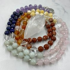 Malas, a string of 108 beads plus a head bead or 'guru' bead, are a traditional tool to use whilst meditating to help the mind focus and count mantras. Our chakra malas have been hand knotted by Georgie whilst listening to chakra and crystal meditation. These malas have 108 crystal beads and a Clear Quartz drop pendant as the guru. Each knot has been made with the intention of aligning the chakras. Crystal Jewelry, Crystal Beads, Clear Quartz, Rose Quartz, 2nd Chakra, Honey Calcite, Chakra Crystals, Ornament Wreath, Plexus Products