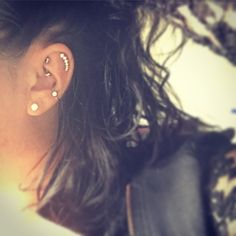 Conch piercing with captive bead ring, rook piercing w curved barbell, helix piercing with crescent diamonds. Conch and rook and helix piercing combo combination.