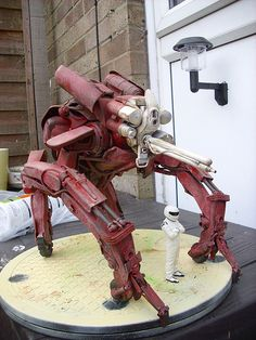 """Scratch built robot, mecha. Made from table top staplers, toy parts, bicycle mudguard and general """"crap"""" and greeblies. Automotive spray for undercoat and base coat, then weathered and detailed with emulsion tester pots."""