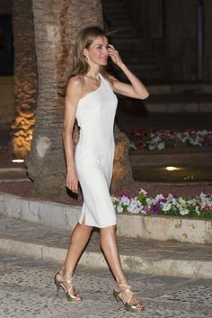 Queen Letizia of Spain looked chic and elegant in a white knee-length dress and gold strappy sandals as she navigated the cobbled streets during an official reception at the Almudaina Palace, 07.08.2014 in Palma de Mallorca, Spain.