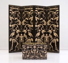 Room divider screen covered with skeletons of animals and a matching trunk.