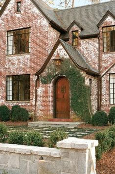 white washed brick exterior, 1930's dramatic roof lines. arched fron wooden door, ivy