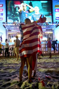 A couple embraces with the American flag wrapped around them as they watch the football game featuring Spain vs. Netherland on the giant screen showing the match at the FIFA World Cup Fan Fest on Copacabana beach on June 13, 2014 in Rio de Janeiro, Brazil. The match was played on the second day of the World Cup tournament and Spain lost 5-1. (Photo by Joe Raedle/Getty Images)