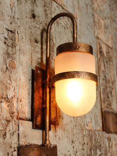 Steel industrial wall light in a distressed antique spray finish with a frosted glass shade and LED lamp.