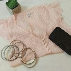 Cute sheer Elle blouse Gently used sheer pink Elle blouse size small but is meant to be worn loose and could probably accommodate small and medium sized.   The 5 small buttons in front are functional. Would definitely need to wear a cami or shirt underneath as this is very sheer. Cute flutter sleeves. Small amount of loose strings on inside of garment but in perfect condition other than that Elle Tops Blouses