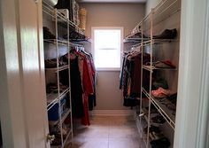 Walk-in closet in master bedroom with window, shelves and bars for hangers.