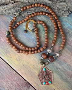 Beautiful raktu seed mala necklace decorated with a Nepalese Buddha pendant