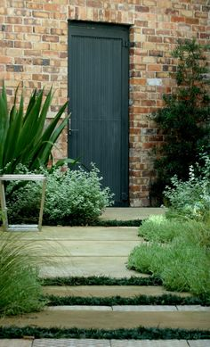 love the old red brick, dark door, and the foliage selection. quiet and elegant