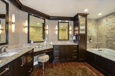 This spacious master bathroom renovation includes a double sink vanity complete with three mirrors and a separate area for applying makeup. A natural stone accent wall is positioned behind the drop-in bathtub, while dark brown wooden cabinetry is paired with neutral granite countertops.