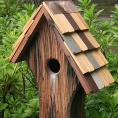 Nottingham Birdhouse With Shingled Roof:  Recall the Old English flavor of Sherwood Forest with this whimsical, rustic cypress bird house. The old English style features a curving asymmetrical design, a bark-like rustic exterior, and a roof with real wooden shingles in various colors. The overall effect adds an idyllic scene of timeless wonder to your yard, and looks particularly enchanting in a woodland setting next to a mossy tree trunk!