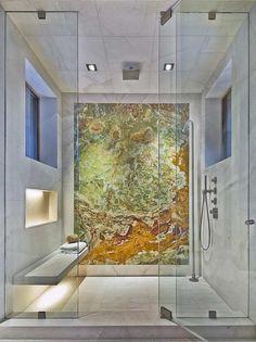 salle de bain moderne décorée d'un carrelage mural et de sol en marbre blanc et un mur d'accent recouvert d'onyx