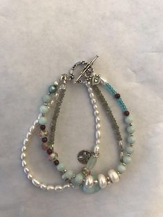 Three strand bracelet includes sterling silver toggle, charms and spacers, cultured pearls, amazonite, apatite, garnet, labradorite, and 4 glass beads adorned with roses. Details: oxidized beaded sterling silver toggle, tiny heart charm, round charm with raised cross relief, a