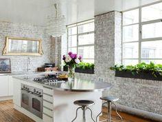 armários de cozinha brancos e design da parede de tijolos pintados de branco
