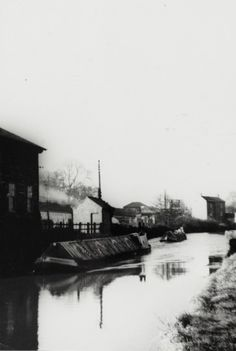 BW192-3-2-2-13-1-481 Pair of British Waterways narrowboats at Weedon on the Grand Union Canal Description Black and white photograph taken from beside the canal looking north, shows the motor in the foreground pulling a butty behind. The stationmasters house and a steam train are visible in the background. Date November 1957