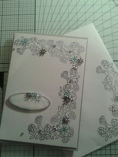Card front with tiny punched flowers and diamantes. I inked the edges of the greeting. I used an oval framelit die for the shape.