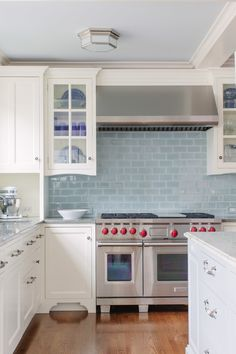 White kitchen design with stainless steel design and light blue subway tile backsplash | Jean Stoffer Design