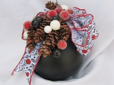 Black ornament decorated with pine cones, red, whit and black berries, white ribbon printed red and black holly and ornaments.