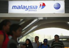 People walk under a Malaysia Airlines sign at Kuala Lumpur International Airport in Sepang March 8, 2014. — Reuters pic