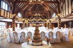The fabulous Tithe Barn at Great Fosters all ready for a Summer wedding reception. Real wedding photography by Surrey photographer Juliet Mckee. #GreatFosters #realweddings #brideandgroom #Englishweddings #Surreyweddingvenues #tithebarn #JulietMckeePhotography #fairynuffflowers #weddingflowers #tablearrangements