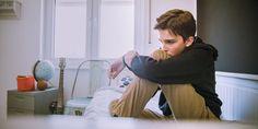 A teenage boy sits on his bed looking depressed