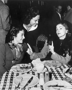 "gregorypecks: "" 1940: Olivia de Havilland in a restaurant with sister Joan Fontaine and Margaret Lindsay. """